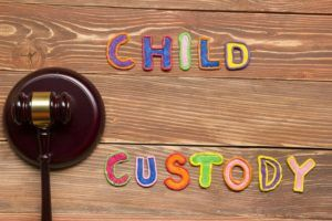 Judge gavel and colourful letters regarding child custody, family law concept
