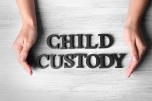Human hands and words CHILD CUSTODY on wooden background, top view